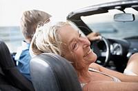 Spain, Senior couple in convertible car, smiling