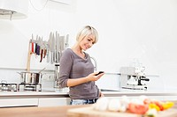 Germany, Bavaria, Munich, Woman using mobile in kitchen