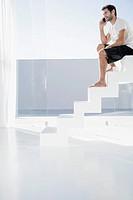 Spain, Mid adult man sitting on stairway, talking on phone