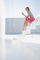 Spain, Mid adult woman sitting on stairway with cell phone (thumbnail)