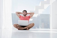Spain, Mid adult man sitting on floor with laptop
