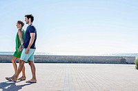 Spain, Mid adult couple walking on pavement (thumbnail)