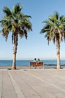 Spain, Mid adult couple sitting on bench