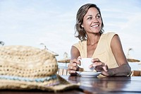 Spain, Mid adult woman in cafe with straw hat