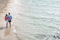 Spain, Seniors couple walking along beach
