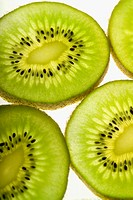 Extreme close_up of four pieces of sliced kiwi fruit, part of