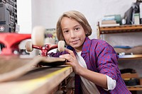 Germany, Leipzig, Boy repairing skateboard, portrait