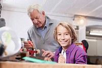 Germany, Leipzig, Grandfather and son repairing skateboard