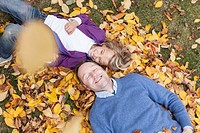 Germany, Leipzig, Father and son lying on leaves, smiling