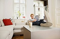 Germany, Berlin, Young man using digital tablet, smiling (thumbnail)