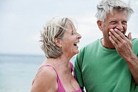 Spain, Senior couple smiling on beach