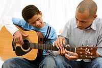 Boy learning guitar with his dad