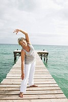 Spain, Senior woman doing yoga on jetty at the sea