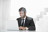 Spain, Businessman using laptop, smiling (thumbnail)