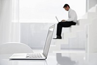 Spain, Businessman using laptop on stairs, laptop in foreground