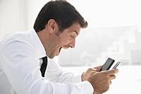 Spain, Businessman confused of using two mobile phone, smiling
