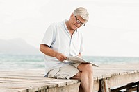 Spain, Senior man reading newspaper on jetty at the sea