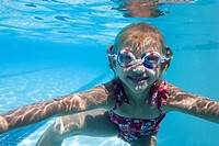 Girl swimming underwater in pool