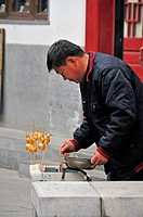 A man stands in the street dipping objects on a stick to colour them gold, beijing china