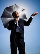 Businessman holding umbrella on a clear day