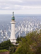Italy, Sailing boats racing across Gulf of Trieste in annual boat race with lighthouse in foreground