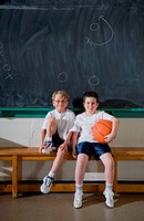 Two boys sitting on gym bench, portrait