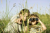 father and son using binoculars in grassy field