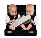 Twin baby boys in briefcase with suits and newspaper
