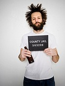 Mug shot of man with cigarette and beer bottle
