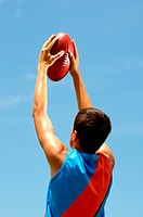 Player holds football up to the sky