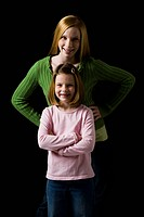 Portrait of a teenage girl with young girl smiling