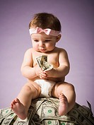 Baby girl sitting on pile of US currency