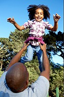 Father tossing daughter up into the air.