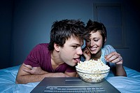 Couple eating popcorn and smiling