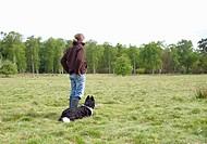 Shepherdess with dog in field.