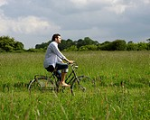 Young man on bike in countryside.