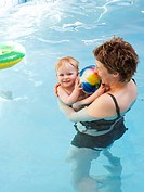 Mother and baby play in pool