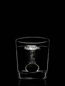 tablet fizzing in glass of water on black