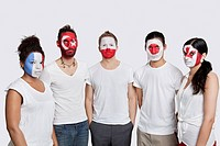 Portrait of serious Multi_ethnic group of friends with various national flags painted on their faces standing against white background