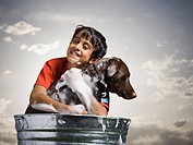 Smiling boy hugging and bathing dog outdoors on cloudy day