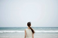 Young woman looking at sea, rear view