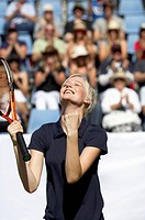 Female tennis player celebrating victory on outdoor court