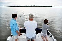 Senior man with son and grandson 10_11 fishing from boat, rear view