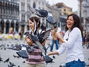 Two women in public square with pigeons laughing