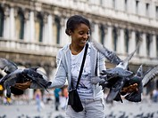 Woman in public square with pigeons smiling