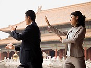 Businesswoman and man doing tai chi outdoors