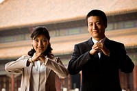 Businesswoman and man doing tai chi outdoors smiling