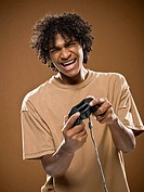 young man in a brown shirt playing a video game.