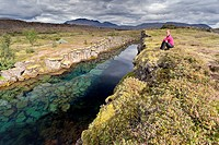 Young woman sitting next to a river, Þingvellir, Pingvellir, Iceland, Europe
