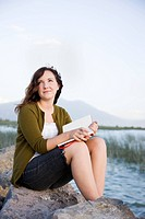 woman sitting by a lake with a notebook